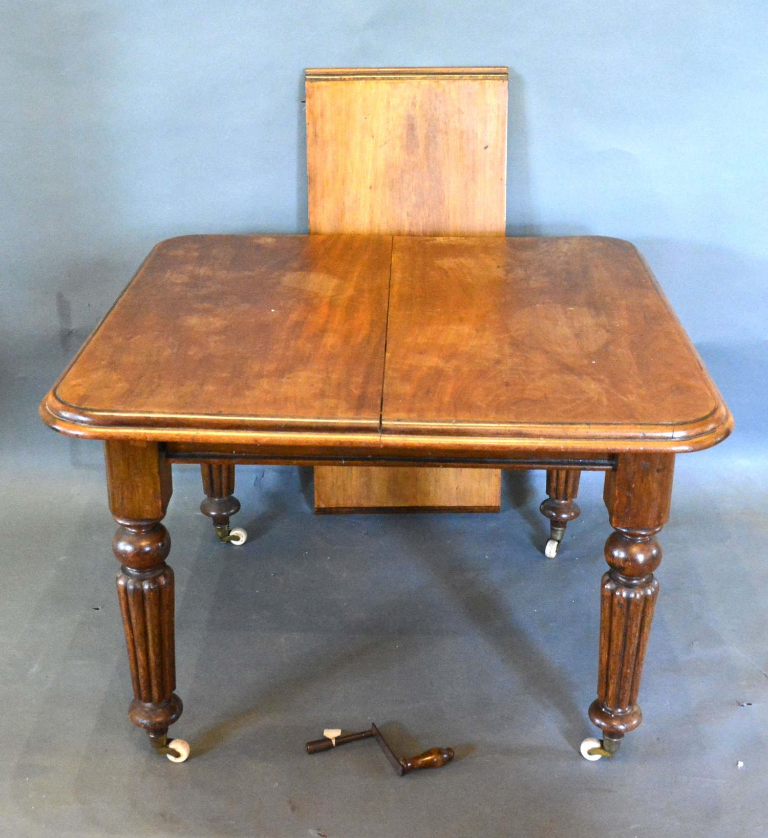 A Victorian Mahogany Wind-Out Extending Dining Table, the moulded top above a plain frieze raised
