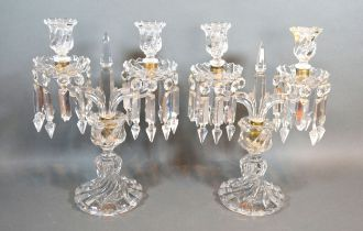 A pair of cut glass two branch candelabrum with facet cut glass drops, 33cms tall
