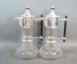 A pair silver plated and glass claret jugs in the style of Christopher Dresser with ebonies handles,