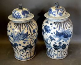 A Pair of Chinese Underglaze Blue Decorated Covered Vases, the covers with dogs of fo surmount and