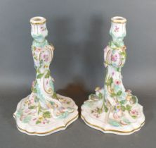 A Pair of Meissen Porcelain Candlesticks each with polychrome foliate encrusted decoration