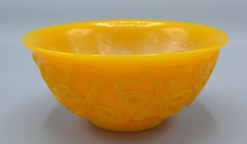 A Chinese Yellow Glass Bowl carved in relief with implements and scrolls, 15.5 cms diameter
