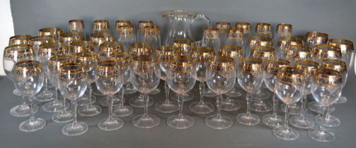 A Cut Glass Drinking Set with gilt scroll banding to include a jug, champagne glasses, wine