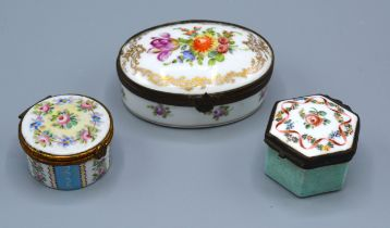 A French Porcelain Pill Box of oval form hand painted with summer flowers and highlighted with
