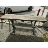 RUSTIC GARDEN TABLE, with large planked top on ornate Victorian cast iron base with masked