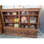 FLEMISH OAK OPEN FRONTED TWIN SECTION BOOKCASE, 4 cupboard base, embellished with copper lionmask
