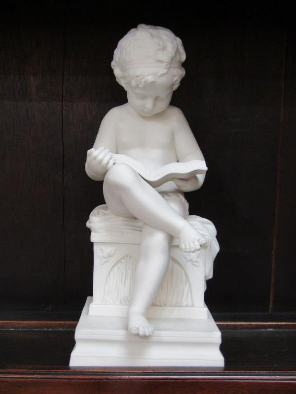 "PARIAN FIGURE, seated Boy reading book, chip to square base, 11"" height"