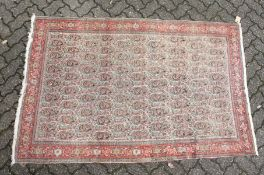 A PERSIAN SENNA RUG, early 20th century, beige ground with Boteh decoration within a red ground