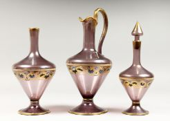 A VENETIAN AMETHYST TINTED GLASS EWER, with gilt and enamel decoration; together with the matching