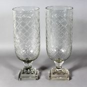 A PAIR OF SLICE CUT CIRCULAR GLASS STORM LAMPS on square stepped bases. 16ins high.