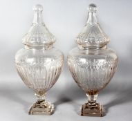 A GOOD LARGE PAIR OF CRYSTAL CUT SWEET JARS AND COVERS on square stepped bases. 21ins high.