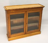 A VICTORIAN LIGHT OAK TWO-DOOR BOOKCASE, with a pair of glazed doors enclosing adjustable shelves,