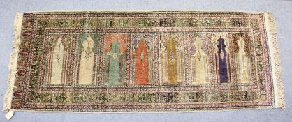 AN UNUSUAL PERSIAN PRAYER RUG, the central panel with eight arches and hanging lamps, within a