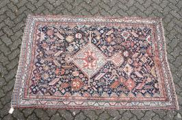 A PERSIAN QASHQAI RUG, early 20th century, dark blue ground with a central diamond shaped panel. 7ft
