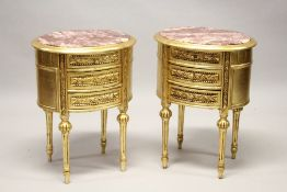 A GOOD PAIR OF THREE DRAWER GILT BEDSIDE TABLES with oval marble tops. 27ins high.