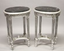 A GOOD PAIR OF SILVERED OVAL TABLES with marble tops. 28ins high.