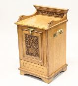 A VICTORIAN OAK COAL PURDONIUM, with carved decoration and brass handles. 2ft 2ins high.