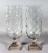 A PAIR OF OVAL CUT CIRCULAR GLASS STORM LAMPS on square stepped bases. 16ins high.