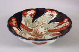 A JAPANESE MEIJI PERIOD IMARI PORCELAIN MOULDED BOWL, with a phoenix in flight amongst raised enamel