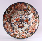 A JAPANESE EDO / MEIJI PERIOD IMARI PORCELAIN CHARGER, decorated with scenes of ikebana displays
