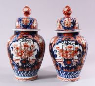 A PAIR OF JAPANESE MEIJI PERIOD IMARI PORCELAIN VASES & COVERS, with panel decoration depicting