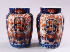 A PAIR OF JAPANESE MEIJI PERIOD IMARI PORCELAIN VASES, with ribbed body, and panel decoration of