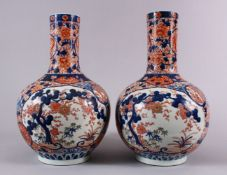 A PAIR OF JAPANESE MEIJI PERIOD IMARI PORCELAIN BOTTLE VASES, decorated with panels of the three