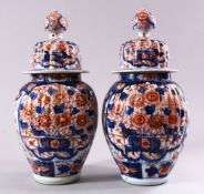 A PAIR OF JAPANESE MEIJI PERIOD IMARI PORCELAIN VASES AND COVERS, with ribbed body's, and panels