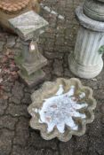 A shell shaped bird bath top together with a classical style pedestal base.