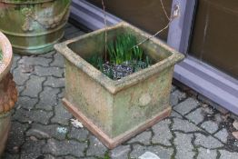 A large square shaped terracotta garden planter.