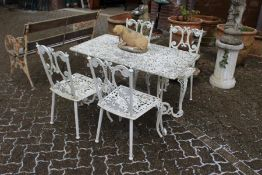 A white painted cast aluminium rectangular patio table and four chairs.