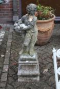 A composite garden figure of a young boy holding a basket of flowers on a pedestal base.