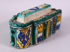 A PERSIAN PAINTED POTTERY INKSTAND AND COVER, the interior with six pen holders and an inkwell, 16cm