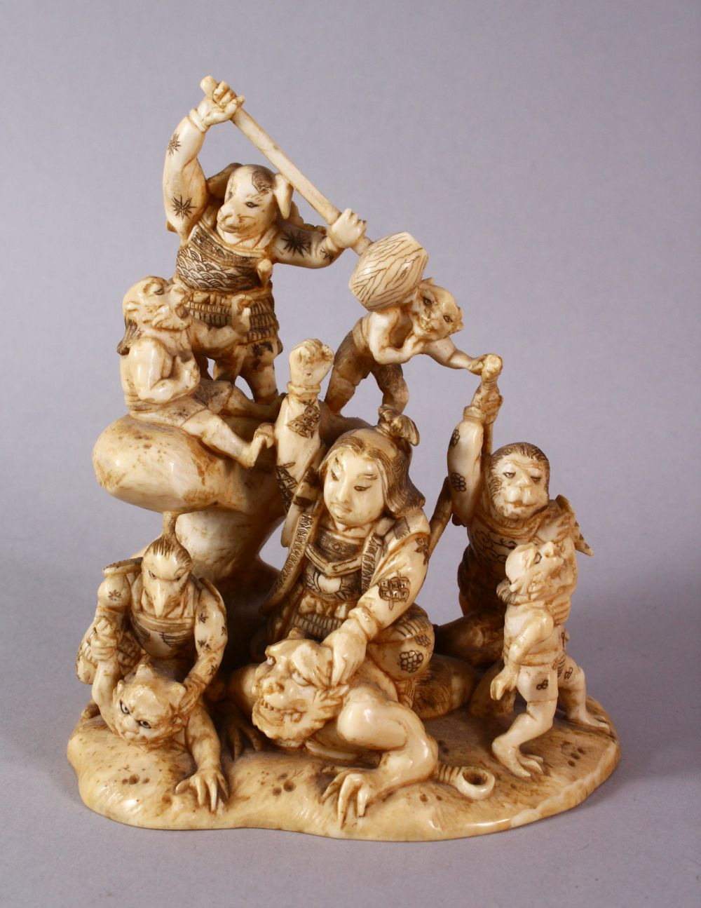A JAPANESE MEIJI PERIOD CARVED IVORY OKIMONO GROUP - depicting figures attacking oni demons, one dog