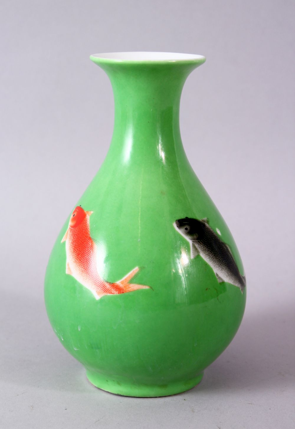 A CHINESE GREEN GLAZED VASE, painted with fish, mark in red, 15cm high.