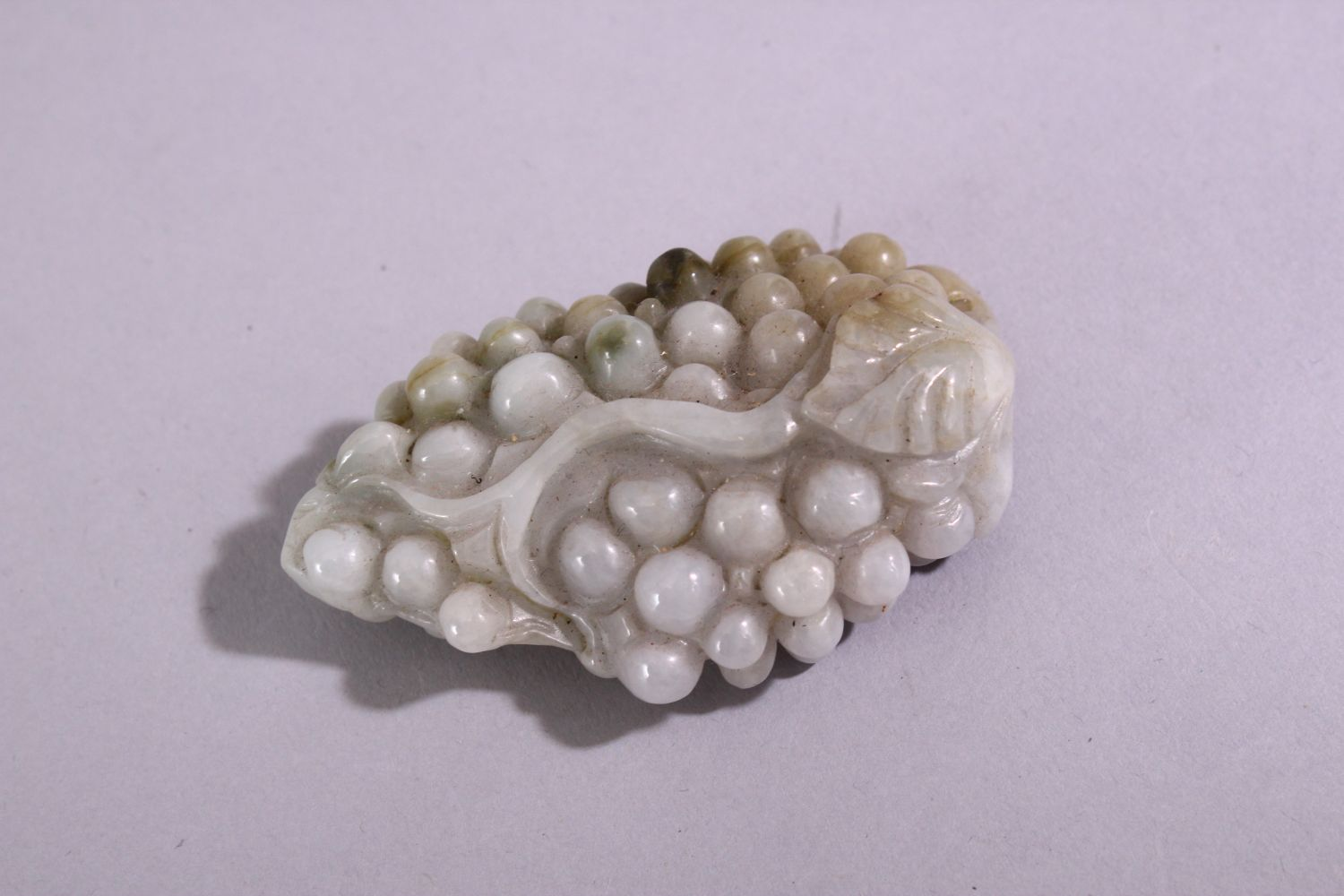 A CHINESE CARVED AND PIERCED JADITE / HARDSTONE AMULET, in the form of a bunch of grapes, 6.5cm x - Image 2 of 3