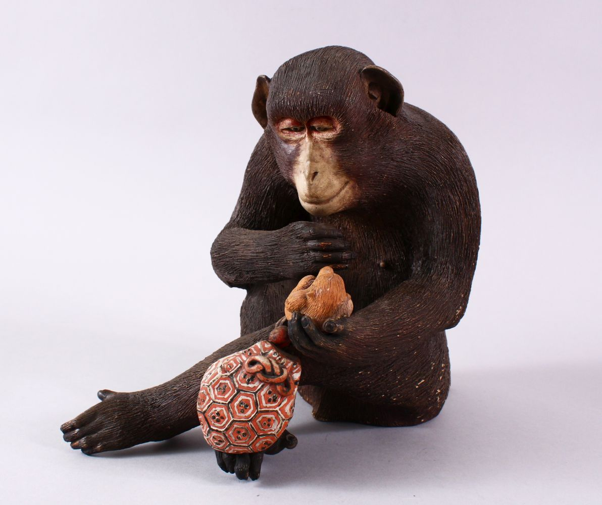 A JAPANESE POTTERY / TERRACOTTA MODEL OF A SEATED MONKEY, the monkey in a seated position holding