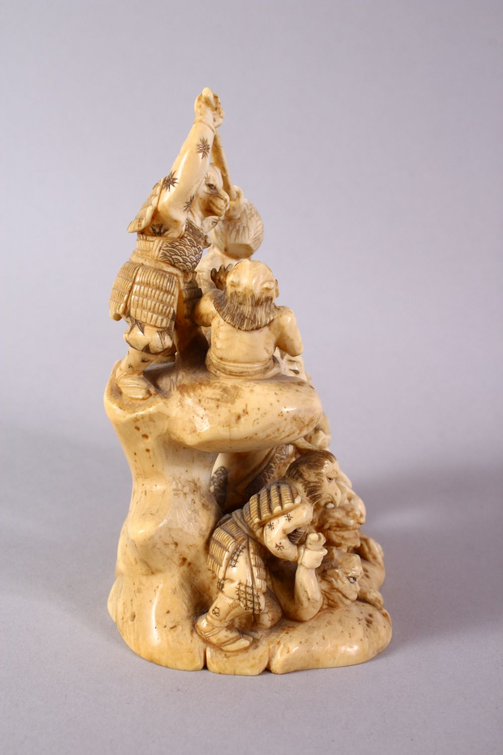 A JAPANESE MEIJI PERIOD CARVED IVORY OKIMONO GROUP - depicting figures attacking oni demons, one dog - Image 3 of 14