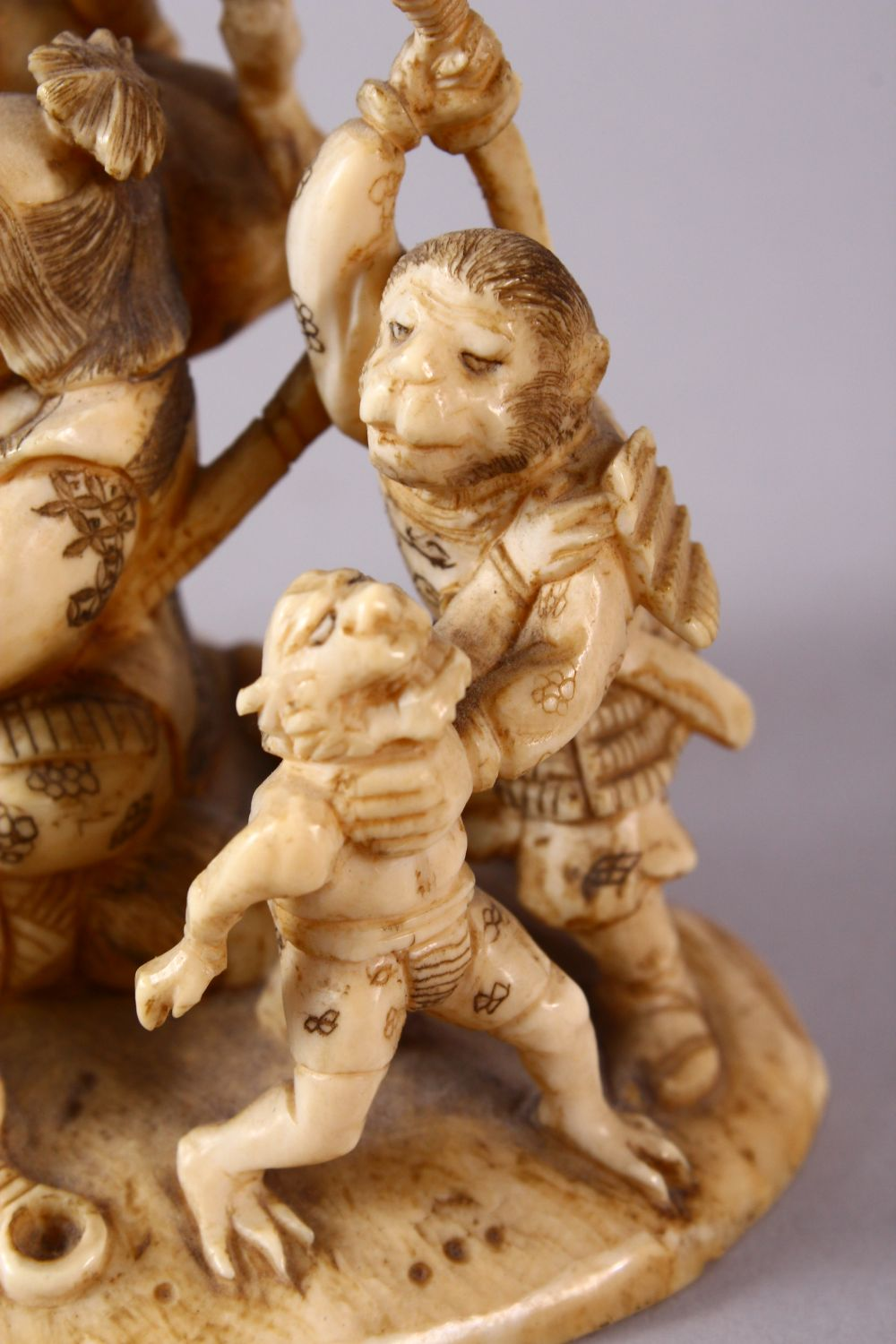 A JAPANESE MEIJI PERIOD CARVED IVORY OKIMONO GROUP - depicting figures attacking oni demons, one dog - Image 11 of 14