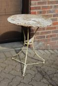 A small white painted wrought iron bistro table.
