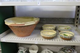 A part glazed terracotta bowl and a set of four hand painted bowls.