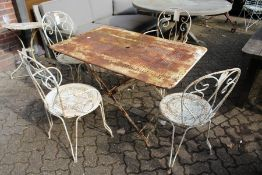 A painted wrought iron rectangular folding table with a set of four wrought iron chairs, two with