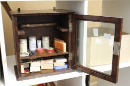 A smoker's cabinet containing snuff and other tobacco related items.