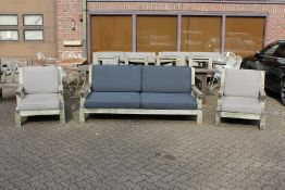 A large teak garden settee with a pair of lounger style armchairs with loose cushions.