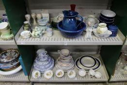Two shelves of part dinner services and other decorative china.