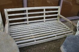 A large hardwood garden settee with loose cushions.