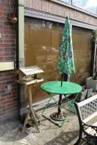 A bird table, a folding table and parasol.
