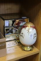 A porcelain egg and a mirrored jewellery chest.
