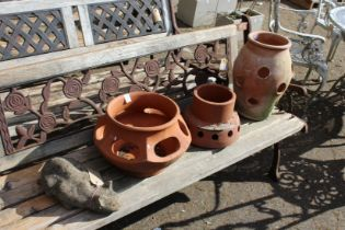 A garden ornament modelled as a cat and three terracotta strawberry pots.