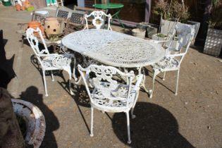 An aluminium patio table and four armchairs.